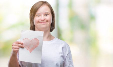 woman holding a paper printed with heart